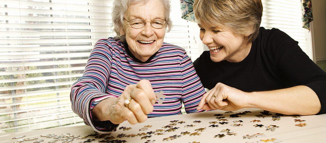 Elderly parent and daughter work on jigsaw puzzle