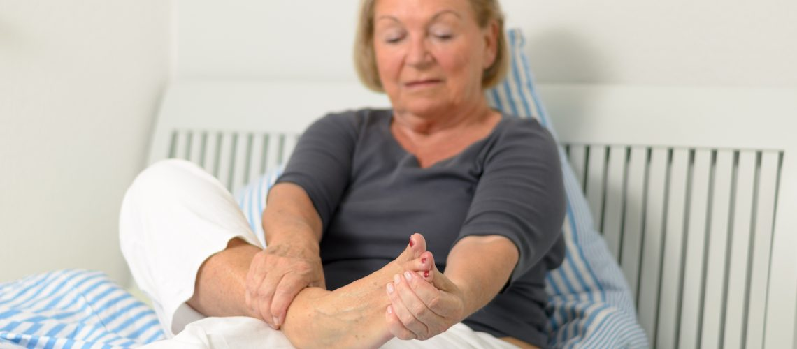 Senior lady massaging her bare foot to relive aches and pains as she sits relaxing against the pillows on her bed